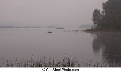 Fisher man row sit in wooden boat on lake covered with dense fog. 4K