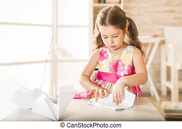 Kinder craft - Adorable little girl playing with origami...