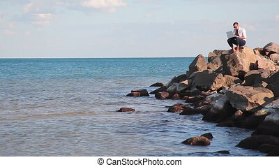 Businessman sitting on large rocks in the sea and does the...