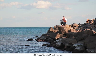 Business man on large rocks by the sea with the joy of...