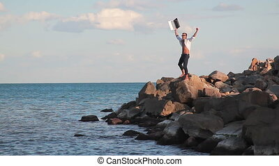 Business man on large rocks by the sea with the joy of victory with a laptop raises his hand up. The joy of victory. Achieving success.