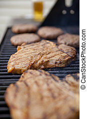 Grilling meat - Steaks and burgers on the grill with a...