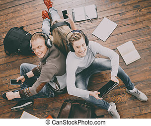 Group of students reading books, and studyin on the floor -...