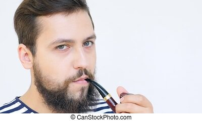 Handsome Seaman with a Beard Smoking a Pipe Close Up