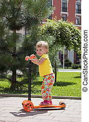 cute little toddler girl riding scooter in the city, kids sport. vertical