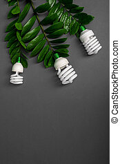 Three LED lamp with green leaf, ECO energy concept, close up. Light bulb on grey background. Saving  and Ecological Environment. Copy space.