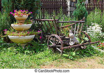 garden decorated with an old wood wagon and flowers