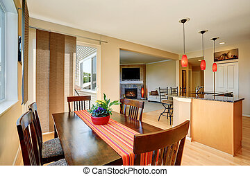 Dining area with wooden table set. Open floor plan. Kitchen...