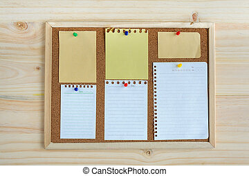 collection of various note papers on cork board with wooden background