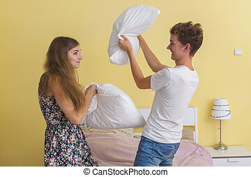Young couple teens , pillow fight - Portrait of young couple...