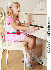 Girl playing the piano - Beautiful little blonde girl plays...