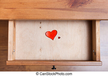 two red glass hearts in open drawer