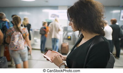 A beautiful lady is checking her passport before the trip. A...