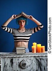 Girl in strapedshirt posing with book on her head. Close up....