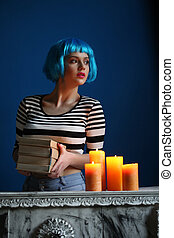 Model in blue wig posing with books and candles. Close up....