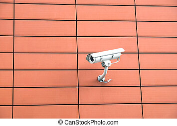 Security camera on orange wall - Security camera mounted on...
