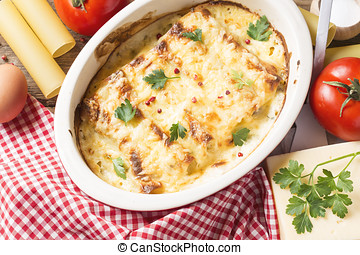 Cannelloni pasta with ingredients on a wood rustic table