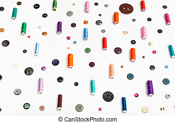 side view of spools of thread and various buttons on white...