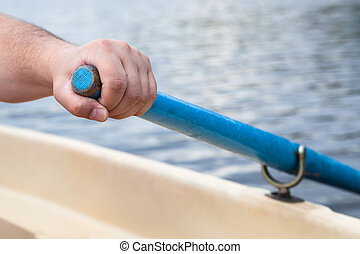 rower's hand holding oar close up while boating