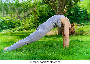 flexibility - Beautiful young woman doing yoga in the summer...