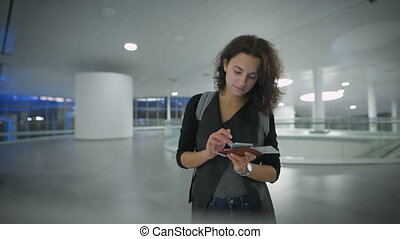 A young beautiful woman is checking new in her phone before...