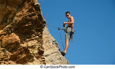 Extreme Climber Hanging On A Rope Resting His Feet Into Rock