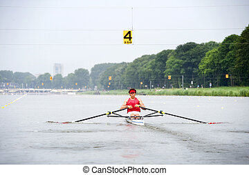 Skiff race - Man, rowing in a skiff during a race at full...