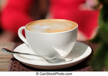 Cup of cappuccino in outdoor cafe, selective focus