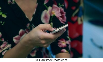 Beautiful young woman's hand using smart phone at...
