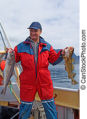 Fisherman with fish on the boat near the Lofoten island