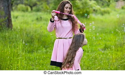 mother sings to her daughter bubbles on nature