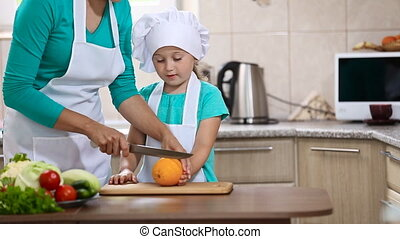Mom and daughter in the kitchen trying to orange