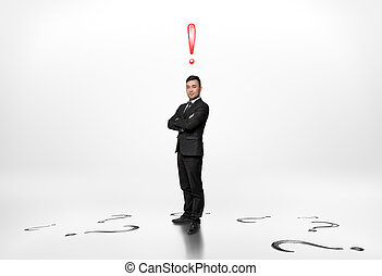 Businessman stands with exclamation mark above him and...