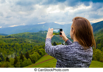 Beautiful view from mountain - Young woman is standing on...