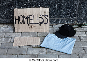 Cardboard for homeless, shirt and cap near the wall in the...