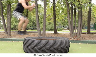 Sportsman working out his body in tire