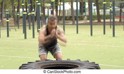 Sportsman working out his body in tire.