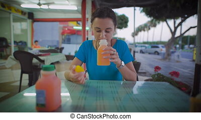 Woman drinking glass of orange juice sitting at a...