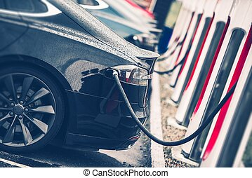 Electric Cars Charging Station Closeup Photo Vehicle...