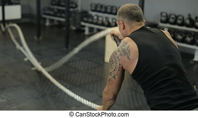 Young adult man doing crossfit workout with ropes led.