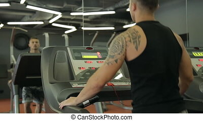 Young athletic men and women exercising and running on treadmill in sport gym.