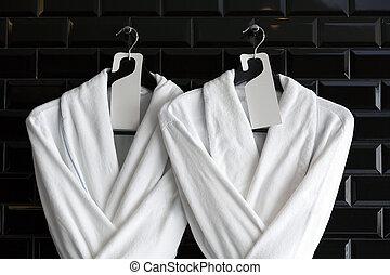 Bathrobe for couple hang on black wall
