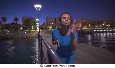 A beautiful woman dancing near the sea and looking at night city panorama