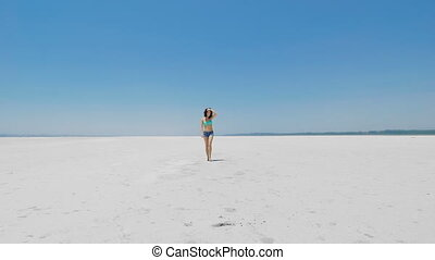 A woman walking on very white salt lake in Cyprus - A young...