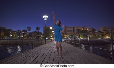 A beautiful woman jumping near the sea and looking at night city panorama