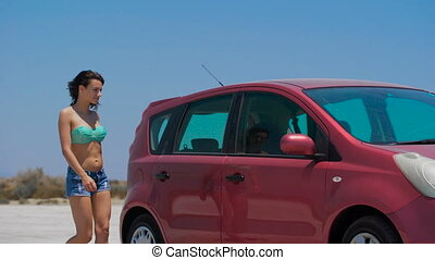 A beautiful girl driving red Nissan Note at the salt lake. -...