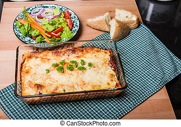 Baked lasagne dish with salad