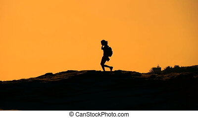 Silhouette of a girl walking on the mountain at sunset