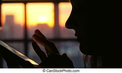 Silhouette of woman use mobile phone in city cafe at sunset on blurred architecture and road background. 1920x1080