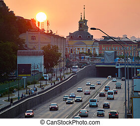 Podil district. Kiev, Ukraine - Cars on a road at sunset....